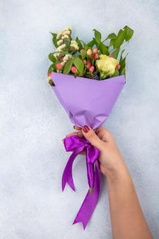 Vista superior de la mano femenina sosteniendo un ramo de rosas con hojas y bayas de hypericum en blanco