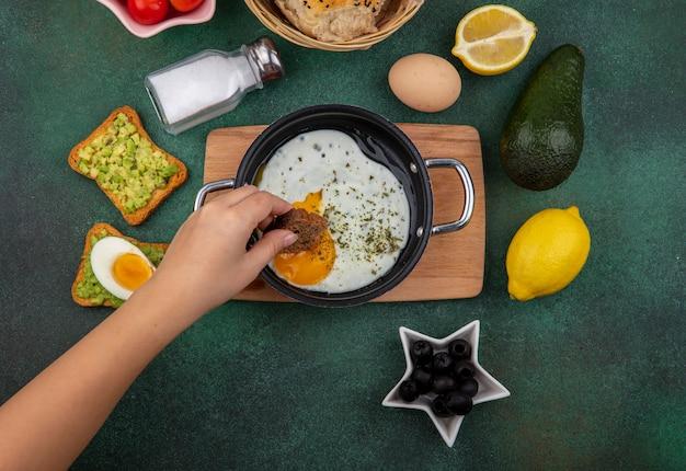 Vista superior de la mano femenina sosteniendo una rebanada de pan con huevo frito en una sartén sobre una placa de cocina de madera con aceitunas negras salero tostadas de limón pan con pulpa de aguacate en gre