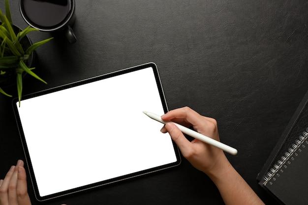 La vista superior de la mano femenina con tableta digital incluye la pantalla de trazado de recorte en el espacio de trabajo creativo oscuro