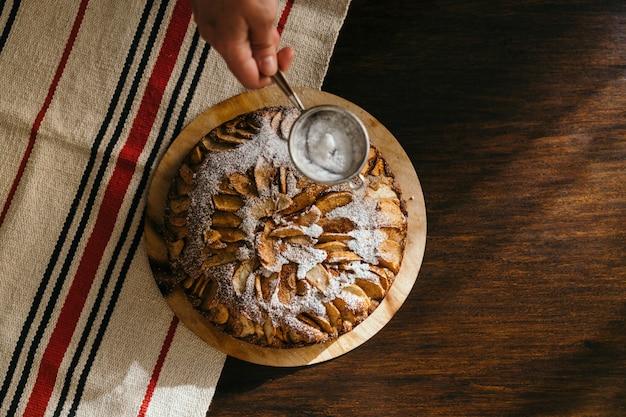 Vista superior de la mano femenina usando un tamiz para espolvorear azúcar en polvo sobre la tarta de manzana natural casera sobre fondo de mesa rústica oscura con espacio de copia