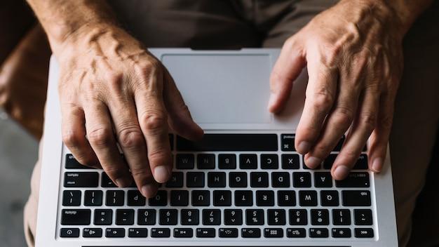 Vista superior de la mano de un hombre escribiendo en el teclado