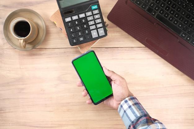 Vista superior de la mano del hombre con teléfono inteligente en el escritorio de oficina