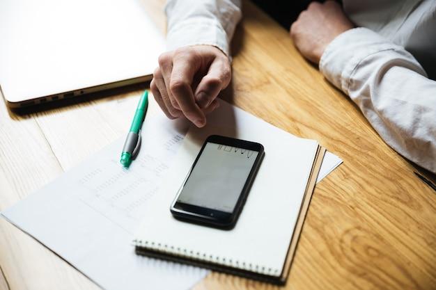 Vista superior de la mano del hombre usando un teléfono inteligente