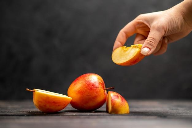 Vista superior de la mano de manzanas rojas picadas y enteras frescas naturales tomando una de las limas sobre fondo negro