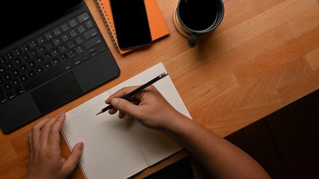 Vista superior de la mano masculina escribiendo en el cuaderno en la mesa de trabajo con tableta, teléfono inteligente y taza de café
