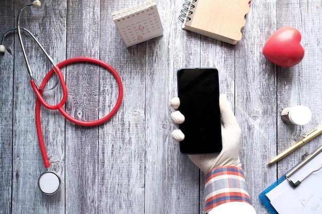 Vista superior de la mano del médico con teléfono inteligente en el escritorio de la clínica