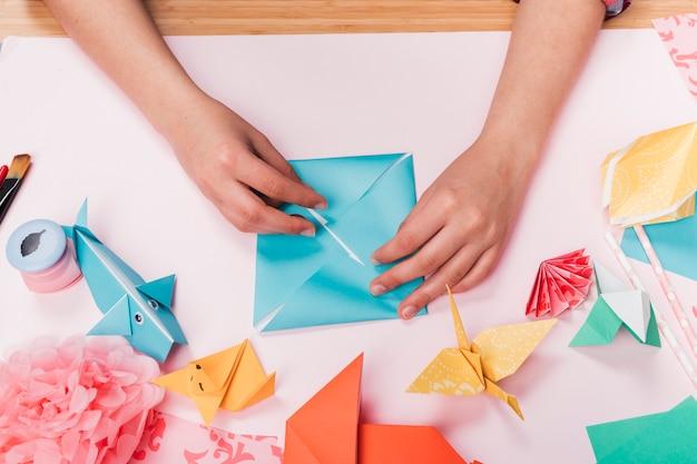 Vista superior de la mano de la mujer que hace el arte del origami sobre la tabla