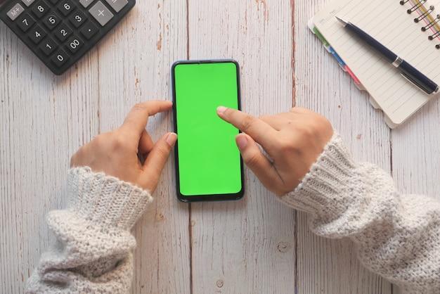 Vista superior de la mano de las mujeres sosteniendo el teléfono inteligente en la mesa