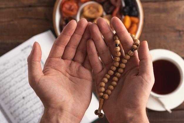 Vista superior de la mano de oración de los hombres con cuentas de madera en la luz del sol
