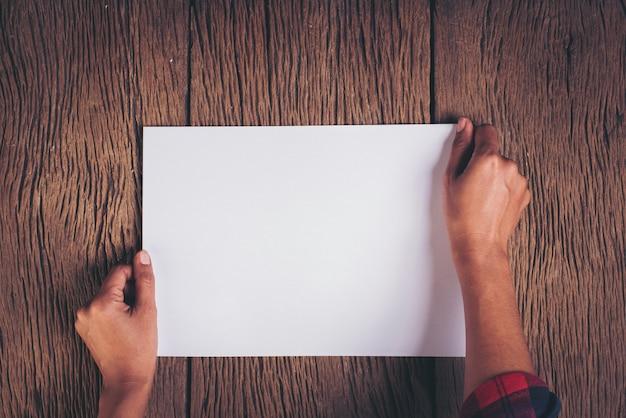 Vista superior mano con papel blanco en blanco.