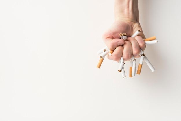 Vista superior de la mano de una persona con cigarrillos rotos sobre fondo blanco