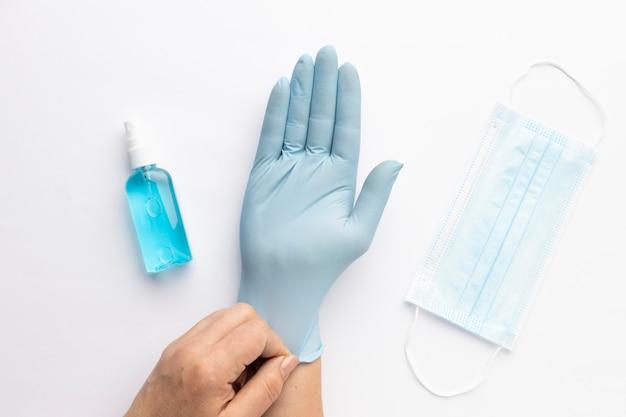 Vista superior de la mano poniéndose el guante con desinfectante de manos y mascarilla médica