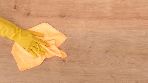 Vista superior de la mano que limpia la superficie de madera con un paño