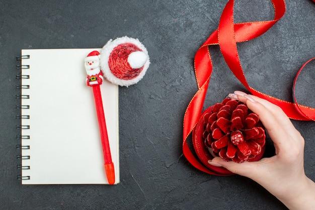 Vista superior de la mano que sostiene un cono de conífera con cinta roja y cuaderno con cinta roja sobre fondo oscuro