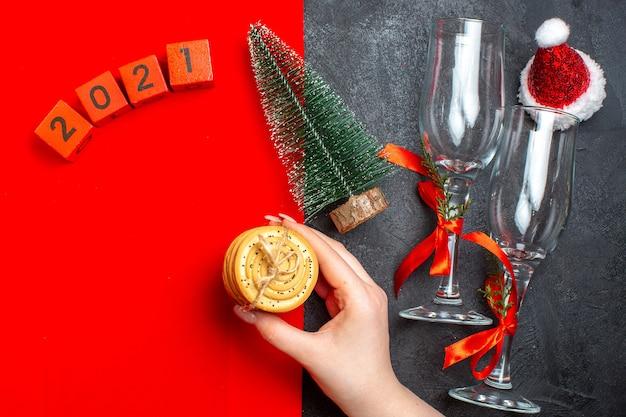 Vista superior de la mano que sostiene las galletas apiladas números de árbol de navidad sombrero de santa claus sobre fondo rojo y negro