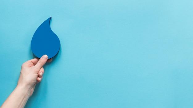 Vista superior de la mano que sostiene la gota de agua de papel