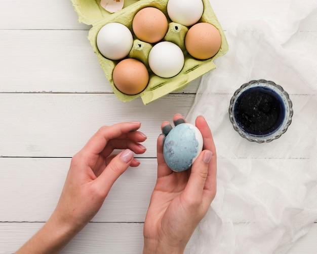 Vista superior de la mano que sostiene el huevo teñido para pascua