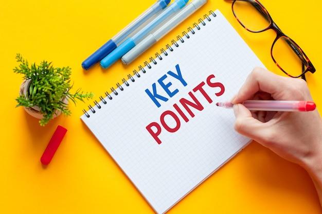 Vista superior, mano que sostiene la lista de puntos clave de escritura de lápiz con cuaderno, bolígrafo, gafas, calculadora y flor verde en la mesa amarilla. concepto de educación y negocios