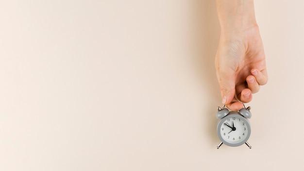 Vista superior de la mano que sostiene el pequeño reloj con espacio de copia