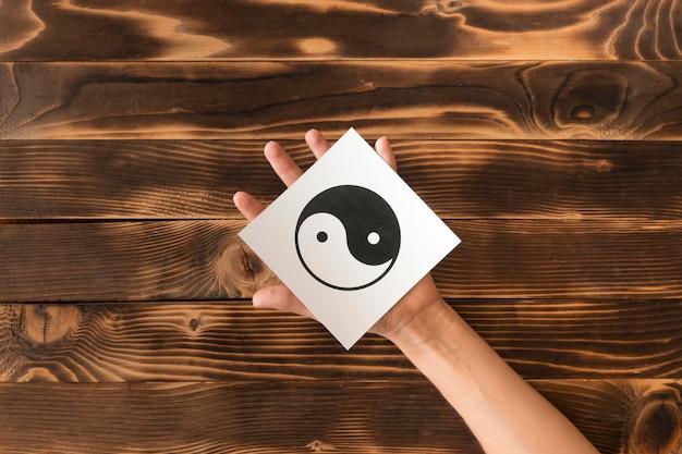 Vista superior de la mano que sostiene el símbolo ying y yang
