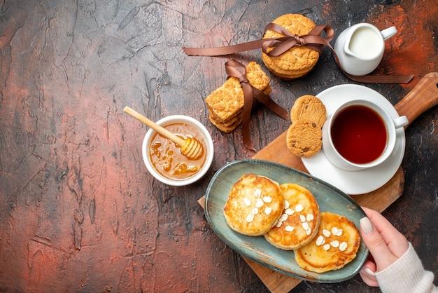 Vista superior de la mano que toma la bandeja con panqueques frescos, una taza de té negro en una tabla de cortar de madera, galletas apiladas con miel, leche en el lado izquierdo sobre una superficie oscura