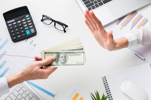 Vista superior de la mano rechazando dinero sobre el escritorio