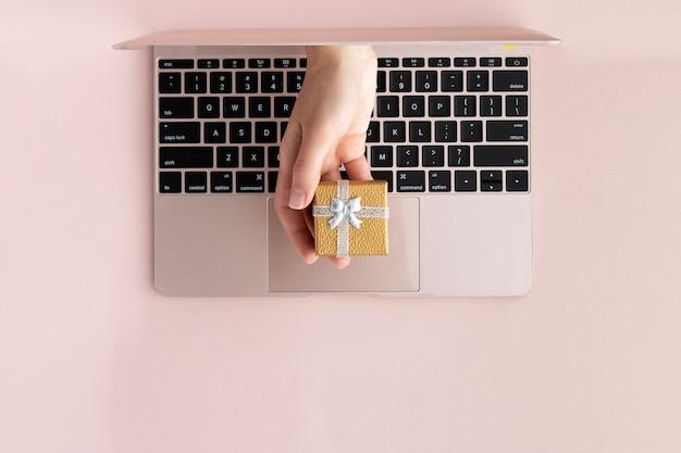 Vista superior de la mano con un regalo de la computadora portátil. plano festivo pone sobre fondo rosa