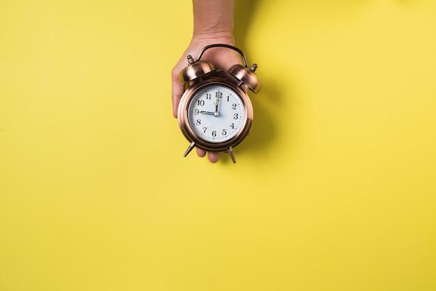 Vista superior de la mano y reloj despertador.