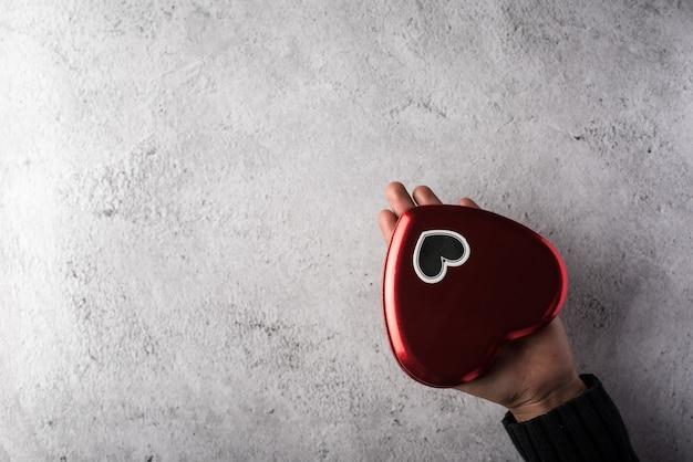 Vista superior mano sosteniendo corazón rojo sobre fondo de pared