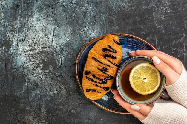 Vista superior de la mano sosteniendo una taza de té negro delicioso croisasant en el lado izquierdo de la mesa oscura
