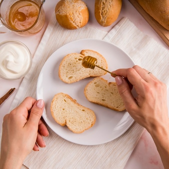 Vista superior mano vertiendo miel sobre rebanadas de pan