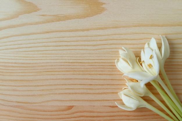 Vista superior de un manojo de flores blancas puras de millingtonia en una mesa de madera de color marrón claro
