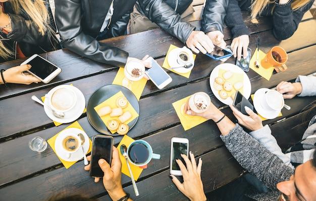 Vista superior de manos de amigos bebiendo capuchino en la cafetería restaurante