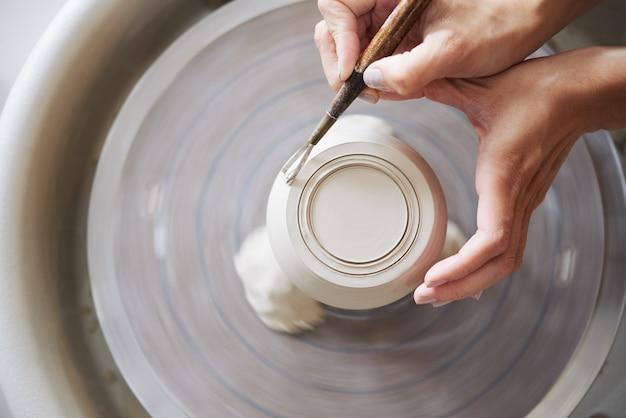 Vista superior de manos anónimas tallando una olla de barro