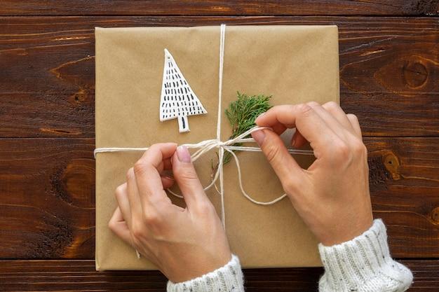 Vista superior de las manos atando el regalo de navidad