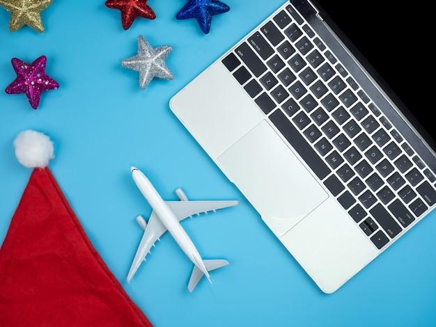 Vista superior de las manos en la computadora portátil, teléfono inteligente, sombrero de santa, tarjeta de crédito, avión y orn de navidad