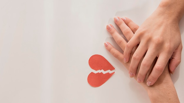 Vista superior manos con corazón roto