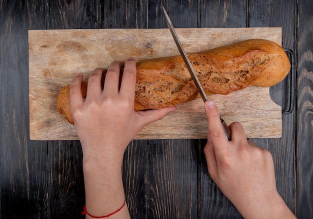 Vista superior de manos cortando baguette negro con cuchillo en la tabla de cortar sobre fondo de madera