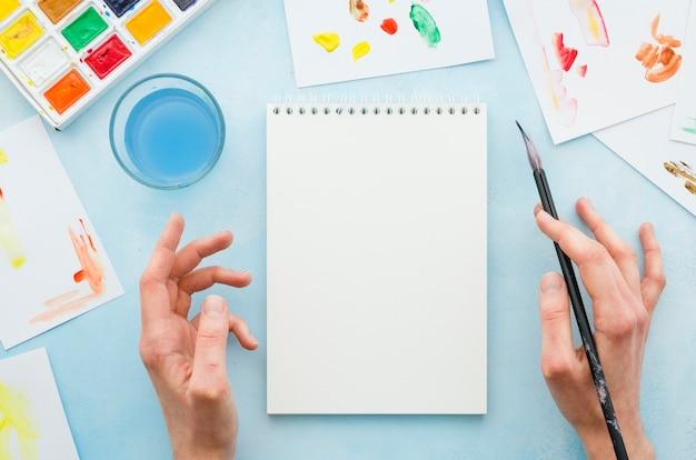 Vista superior manos y cuaderno rodeado por elementos de pintura