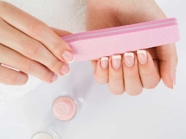 Vista superior manos cuidadas sosteniendo lima de uñas