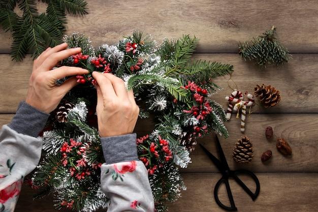 Vista superior manos decorando corona de navidad