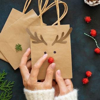Vista superior de las manos decorando lindas bolsas de regalo de navidad de renos