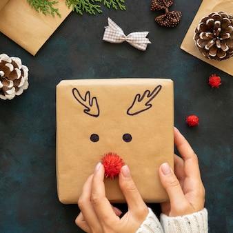 Vista superior de las manos decorando un regalo de navidad con un lindo reno