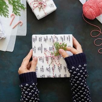 Vista superior de manos decorando regalo de navidad con planta
