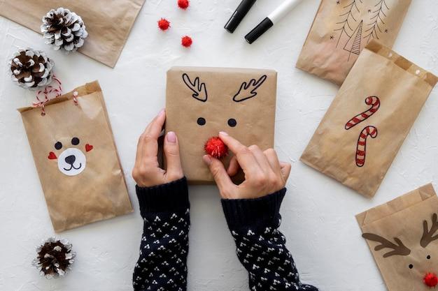 Vista superior de manos decorando regalo de navidad