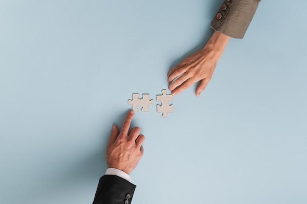 Vista superior de manos de empresaria y empresario uniendo dos piezas de rompecabezas