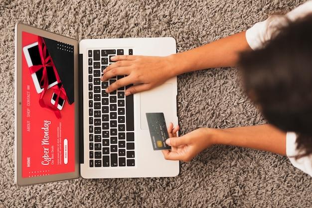 Vista superior de las manos escribiendo en la computadora portátil y sosteniendo una tarjeta de crédito simulacro
