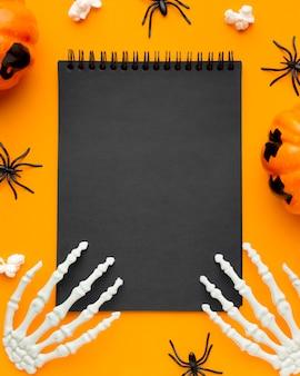 Vista superior de las manos del esqueleto en el bloc de notas para halloween