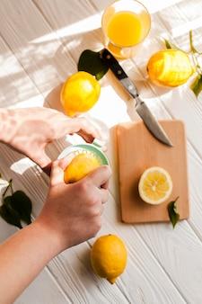 Vista superior manos exprimiendo limón
