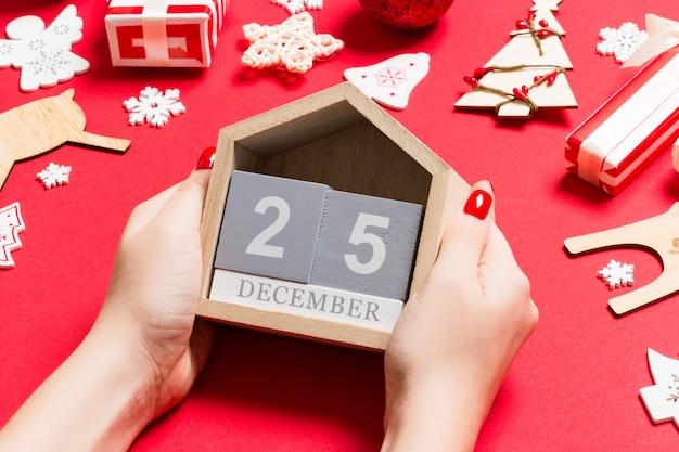 Vista superior de manos femeninas con calendario. el veinticinco de diciembre. decoraciones navideñas. concepto de tiempo de navidad
